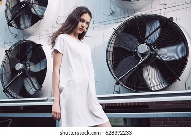 Streetstyle, fashion. Young girl in white dress standing on propellers background