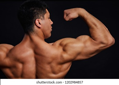 the strengh of arms. bodybuilder demontrating his strength. close up cropped back view photo. isolated black background.
