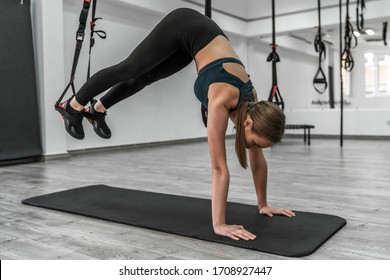 Strength and concentration. Young blonde  woman in sportswear exercising at gym with trx.
