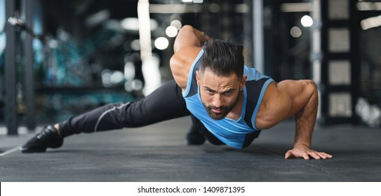 Strength exercise. Muscular man doing push ups on on hands in gym, panorama