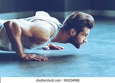 Strength and motivation. Side view of young handsome man in sportswear doing push-up at gym