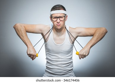 Strength skinny man exercise with expander doing fitness - training, isolated on gray white background
