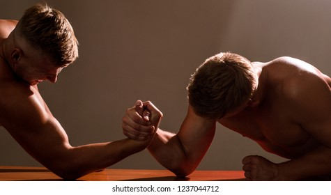 Strength and stability. Men competitors try to win victory or revenge. Twins men competing till victory. Twins competitors arm wrestling. Strength skills. Revenge in sport.