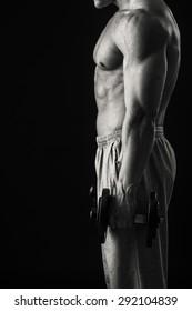 Strength training bodybuilder. Training with dumbbells.