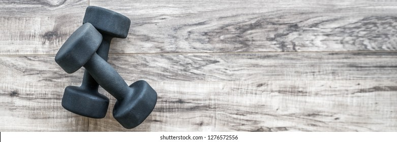 Strength training exercise gym concept: dumbbell weights on wood floor fitness. Weight loss and health. Banner panorama with space on floor texture at home.