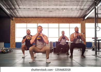 Strength Training in Gym. Small Group of Muscular Male Adults Training Squats With Weights. Teamwork, Sports and Fitness