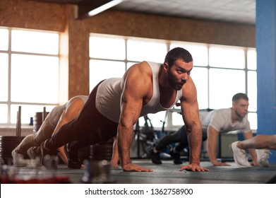 Strength Training in Gym. Small Group of Muscular Male Adults Warming Up Training Push Ups. Teamwork, Sports and Fitness