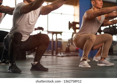 Strength Training in Gym. Small Group of Muscular Male Adults Warming Up Training Squats. Teamwork, Sports and Fitness