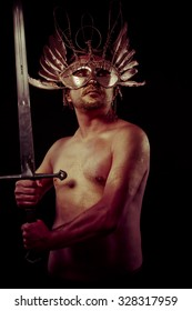 Strength, warrior with golden mask and huge iron sword, body covered with gold dust