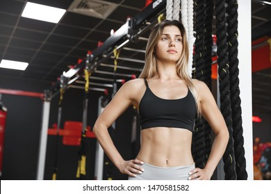 Strength, women and sports concept. Motivated athletic sportswoman in activewear bra, standing confident hands on hips, fitness instructor waiting students near crossfit battle rope equipment