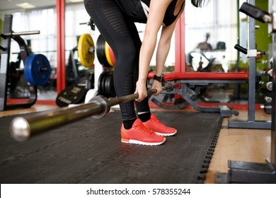 Strength workout. Side view close-up shot of  fit young woman in sportswear working out with barbell at gym