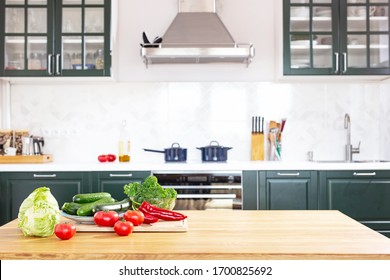 strengthening immunity during the coronavirus pandemic. Fresh vegetables on the table on a background of green kitchen. Kale cabbage, tomatoes, zucchini, cucumbers, paprika,  cabbage. Avitaminosis.
