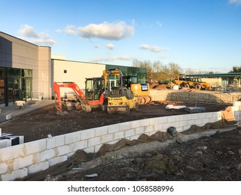Strensham Motorway Services, M5, Worcestershire - March 2018: Wide angle view of a building site showing a new block wall and mini excavators in the background