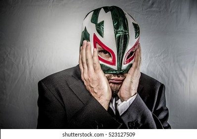 Stress, Angry businessman with mask of Mexican fighter, dressed in suit and tie