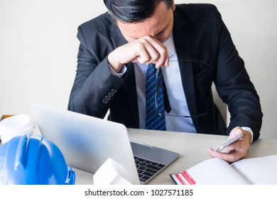 Stress Asian engineer manager with black suit get painful feelings and sit at working table in office when check bad news from smart or mobile phone. Construction project delay. Headache business man.