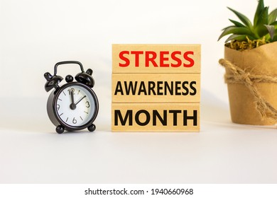 Stress awareness month symbol. Wooden blocks with words 'Stress awareness month'. Beautiful white background. Black alarm clock. Psychological, business and stress awareness month concept. Copy space.