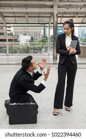 Stress Business man  kneel to his woman boss to ask for sympathy after  he not get promote or be punished outside office building. Sad working guy against angry female manager. Work in pressure.