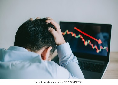 Stress Business man look at to the laptop show financial market chart graphic going down.  Stock market concept.