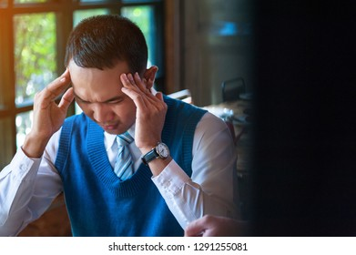 Stress Businessman holding his head with his hands while working at the office.