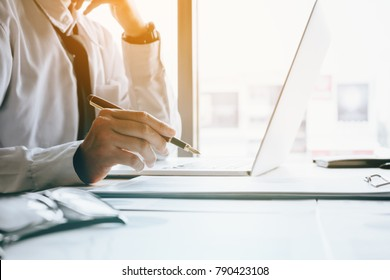 Stress businessman at office room holding pen pointing summary report graph and analyze with using laptop for searching information data.