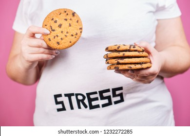 stress, eating problems, bulimia, compulsive overeating, sugar addiction, weight gain. overweight woman with stack of chocolate cookies