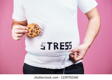 stress, eating problems, bulimia, compulsive overeating, sugar addiction, weight gain. overweight man with chocolate cookies and measuring tape