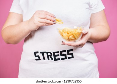 stress, eating problems, bulimia, compulsive overeating, weight gain. overweight woman with portion of french fries