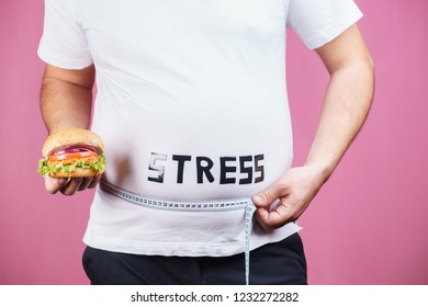 stress, eating problems, compulsive overeating, weight gain. overweight man with fresh appetizing burger and measuring tape