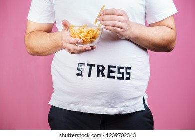 stress, eating problems, compulsive overeating, fat food, weight gain. overweight man with appetizing french fries