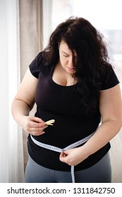 stress, eating problems, compulsive overeating, fat food, weight gain. overweight woman with appetizing french fries and measuring tape on her waist