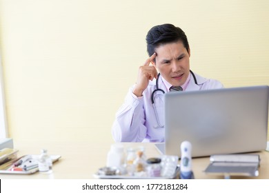 Stress headache male asian doctor working in clinic office at hospital