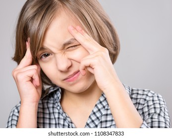 Stress and headache - teen girl having migraine pain. Cute child suffering from a headache. Unhappy caucasian teenager touching her head, on gray background.