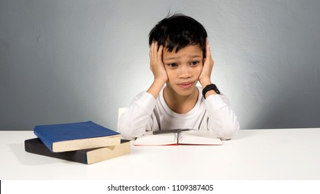 Stress kid doing homework.Boy at study table doing homework with stress action.Lazy boy doing homework with stressed face.