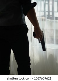 Stress man holding gun on hand . Robber or gangster,thief holding gun in hand. Man holding a gun in his hand ready to shoot