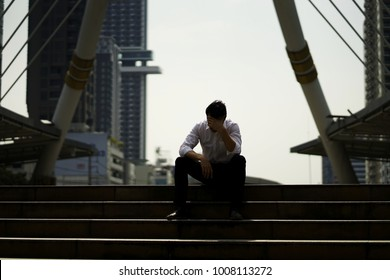 The stress man sitting alone on the stair outdoor. Young business man crying abandoned lost in depression sitting on stairs suffering emotional pain, sadness, looking sick. Young desperate man.
