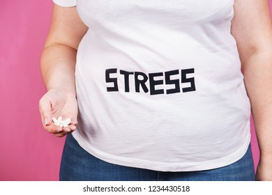 stress, mind problems, bulimia, compulsive overeating, weight gain. overweight woman with sedative pills