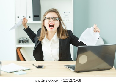 Stress, office, hysteric, people concept - aggressive woman with a lot of work in office