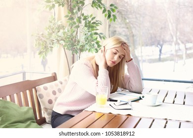 Stress and pain at work. Young businesswoman suffering from headache while drinking coffee