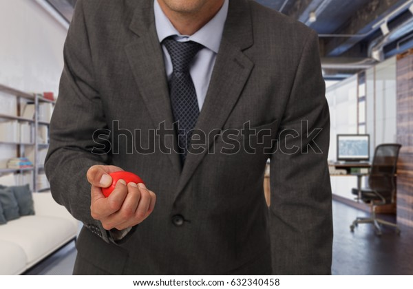 Stress relief concept. Skeptic and upset business man trying to calm down with anti stress rubber ball in an office.