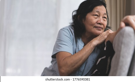 Stress and thinking asian elderly woman is lonely sitting on the sofa near the window, concept of mental and healthcare of older people in family.