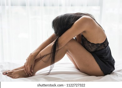 Stress thoughtful sexy Asian woman with black pajama dress sitting on white bed. Serious girl bend down the head with sad feeling after breaking up with husband.