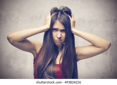 Stress. Woman stressed is going crazy pulling her hair in frustration. Close-up of young businesswoman on grey