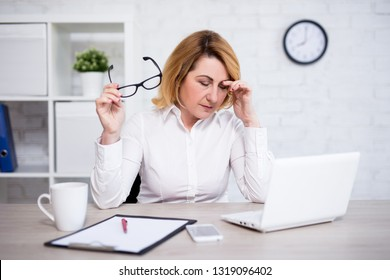 stress and work concept - stressed or tired mature female doctor sitting in modern office