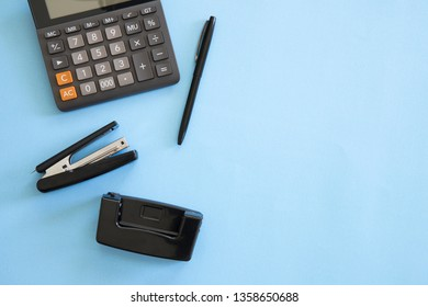 Stress at work in the office concept with calculator, phone, pen and paperwork