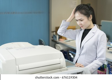 stress young asian businesswoman looking at paper stuck in printer at office