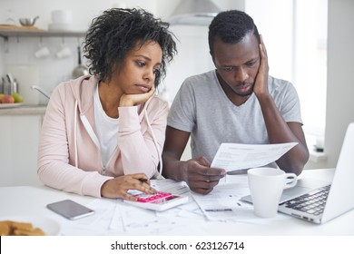Stressed african american couple looking frustrated, having no money to pay off their debts, managing family budget together, sitting home at kitchen table with lots of papers, laptop and calculator