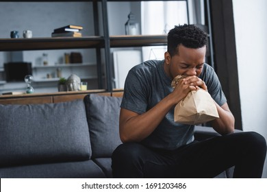 stressed african american man breathing with paper bag while having panic attack at home