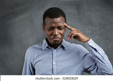 Stressed African businessman with painstaking expression struggling to remember something, closing his eyes tight and pressing finger on his temple as if having bad headache. Short-term memory loss