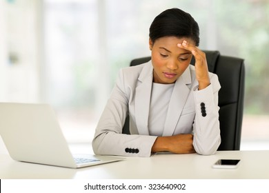 stressed african businesswoman sitting in office