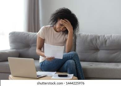 Stressed african woman holding papers calculate domestic bills at home worried about bankruptcy financial problem bank debt, depressed sad black lady frustrated about lack of finances sit on sofa